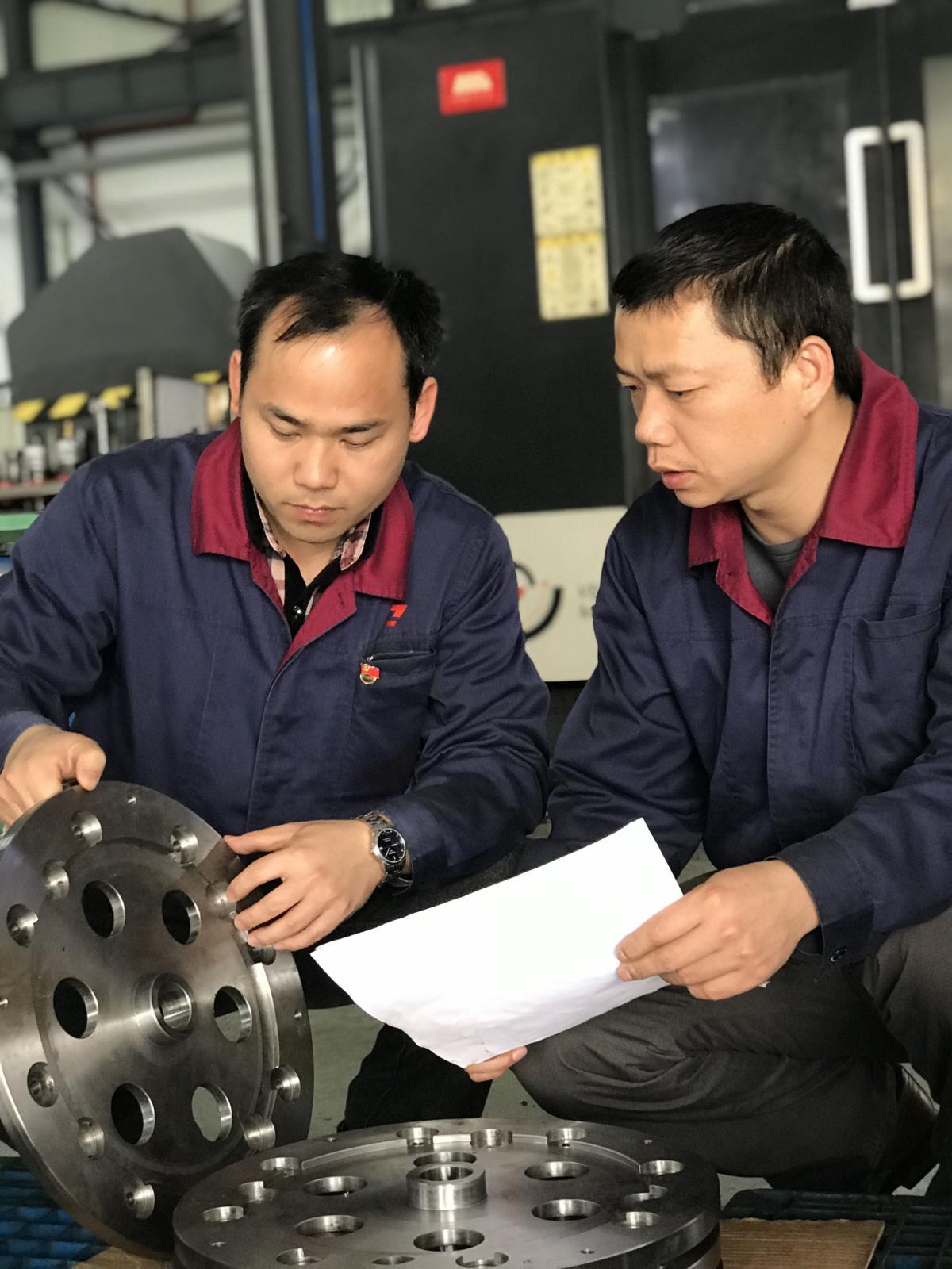 甘达淅老师在与徒弟龚荣探讨新产品转向轴工艺.jpg